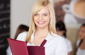 Confident Cafe Waitresses Holding Menu In Cafe